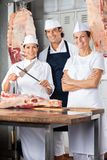 Confident Butchers Standing At Counter Royalty Free Stock Photos