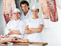 Confident Butchers Standing Together At Counter Stock Photo