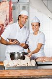Confident Butchers Working At Shop Counter Stock Photo