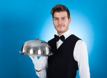 Confident butler carrying tray Stock Photo