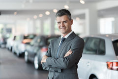 Confident car salesman at the showroom Stock Image