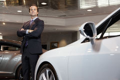 Confident car salesperson standing with arms crossed Royalty Free Stock Image