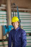 Confident Carpenter Against Vertical Saw Machine Royalty Free Stock Images
