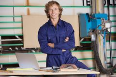 Confident Carpenter With Arms Crossed In Workshop. Portrait of confident carpenter with arms crossed standing in workshop Stock Images