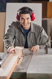 Confident Carpenter Cutting Wooden Plank With Stock Images