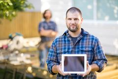 Confident Carpenter Displaying Digital Tablet With Royalty Free Stock Images