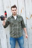 Confident carpenter holding hand drill Royalty Free Stock Images