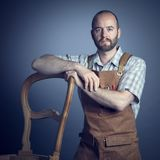 Confident carpenter portrait. Portrait of caucasian wood worker with apron studio shot stock images