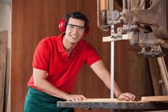 Confident Carpenter Using Bandsaw To Cut Wood Stock Images