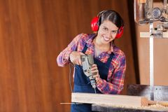 Confident Carpenter Using Drill Machine In Stock Images