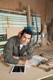 Confident Carpenter Working On Blueprint In Royalty Free Stock Photography