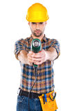 Confident carpenter. Confident young male carpenter in hardhat stretching out drill and looking at camera while standing against white background Royalty Free Stock Images