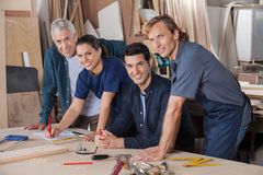 Confident Carpenters Working At Table In Workshop Royalty Free Stock Photo