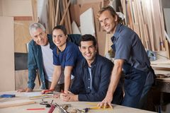 Confident Carpenters Working At Workshop Table Royalty Free Stock Images