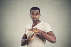 Confident casual man showing time out gesture with hands. Portrait young confident casual man showing time out gesture with hands isolated grey wall background Royalty Free Stock Photo