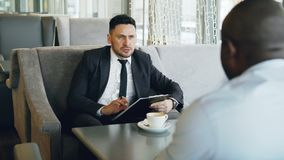 Confident Caucasian businessman in formal clothes taking job interview with his African American employee in glassy cafe. Portrait of bearded Caucasian stock video footage