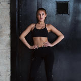 Confident Caucasian fitness model in black sportswear standing hands on hips looking at camera posing against black door Royalty Free Stock Image