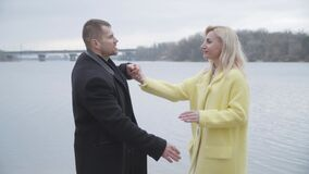 Confident Caucasian man spinning blond woman in sensual dance on riverbank. Middle shot of happy adult married couple