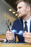 Confident ceo. Young ceo in formalwear holding his eyeglasses Royalty Free Stock Images