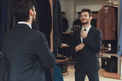 Confident cheerful man ties up tie in showroom of men business clothes store. Confident cheerful man ties up tie in showroom of man business clothes store Royalty Free Stock Images