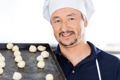 Confident Chef Carrying Baking Sheet With Dough Royalty Free Stock Photography