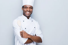 Confident chef. Cheerful young African chef in white uniform keeping arms crossed and smiling while standing against grey background Royalty Free Stock Photo