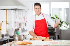 Confident Chef Gesturing Thumbsup While Rolling. Portrait of confident male chef gesturing thumbsup while rolling ravioli pasta sheet at counter in commercial Stock Photo