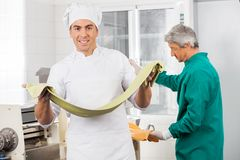Confident Chef Holding Pasta Sheet With Colleague Royalty Free Stock Photos