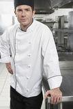 Confident Chef In Kitchen. Portrait of a confident male chef standing in the kitchen Stock Photo