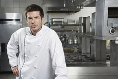 Confident Chef In Kitchen. Portrait of a confident male chef standing in the kitchen stock image