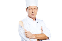 Confident chef. Confident mature chef in white uniform keeping arms crossed and smiling while standing against white background Royalty Free Stock Photos