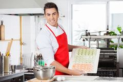 Confident Chef Presenting Raw Ravioli Pasta On Stock Image