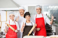 Confident Chef Team Gesturing Thumbsup In Kitchen Stock Images
