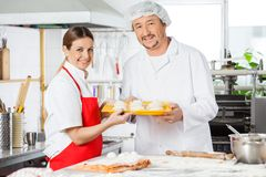 Confident Chefs Holding Pasta Tray In Kitchen Stock Image