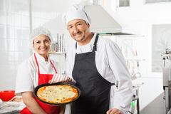 Confident Chefs With Pizza Pan At Commercial Stock Images