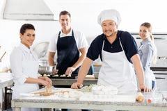 Confident Chefs Preparing Pasta At Kitchen Royalty Free Stock Photo