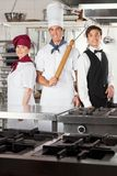 Confident Chefs And Waiter In Kitchen Royalty Free Stock Photography