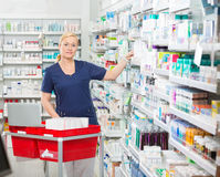 Confident Chemist Arranging Medicines In Shelves Royalty Free Stock Image