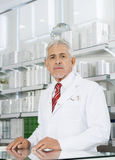 Confident Chemist Standing At Counter In Pharmacy Stock Photo