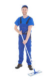 Confident Cleaner Mopping Over White Background. Portrait of confident young cleaner mopping over white background Royalty Free Stock Photography
