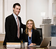 Confident co-workers posing at desk Royalty Free Stock Photos