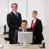 Confident co-workers standing at desk. Happy, confident co-workers standing at desk Stock Images