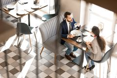 Confident colleagues eating and chatting in restaurant. Confident handsome businessman in smart casual clothing drinking coffee and eating salad while talking to stock images