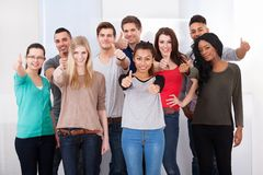 Confident College Students Gesturing Thumbs Up. Group portrait of confident multiethnic college students gesturing thumbs up in classroom Stock Images