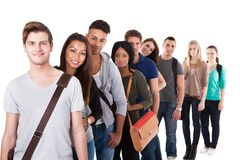 Confident college students standing in a queue. Portrait of confident multiethnic university students standing in a queue against white background stock photos