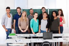 Confident college students standing together in classroom Stock Image