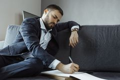 Man Working In Office Doing Notes. Confident concentrated handsome bearded businessman in a trendy suit writes down important ideas in a notebook sitting on a royalty free stock photography