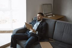 Man Working In Office Doing Notes. Confident concentrated handsome bearded businessman in a trendy suit writes down important ideas in a notebook sitting on a stock image