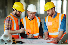 Confident Construction Team Checking Plans on Site. Team of construction workers wearing protective helmets and vests discussing project details with executive Stock Image