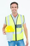 Confident construction worker holding gloves and hardhat Royalty Free Stock Image
